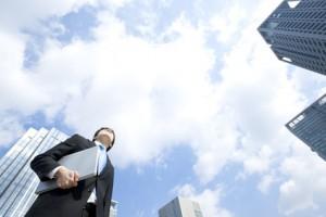 ノートパソコンを抱え空を見上げるビジネスマã